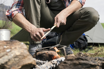 Low section of man cutting stick over bonfire at campsite