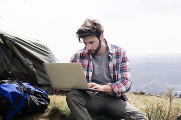 Man using laptop at campsite on hill against clear sky
