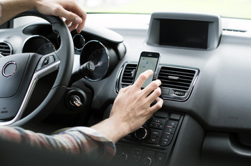 Cropped image of man using GPS on smart phone in car