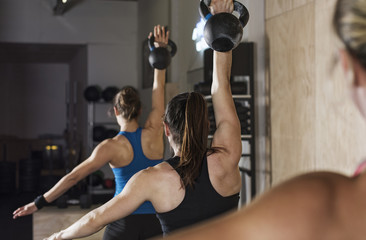 Rear view of female athletes lifting kettle bells in gym