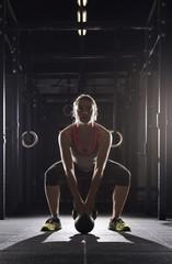 Full length of determined female athlete lifting kettle bell in gym