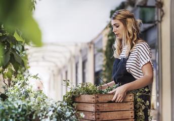 Florist carrying basket of leaves