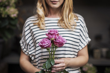 Midsection of woman with pink roses in flower shop