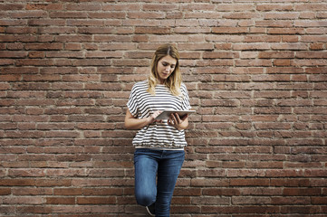 Woman using tablet computer while standing against brick wall