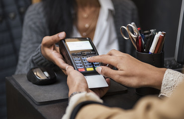 Woman doing credit card payment at checkout counter in store