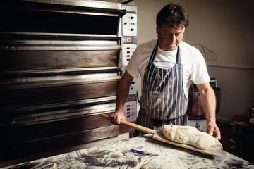 Baker holding bread on spatula in kitchen