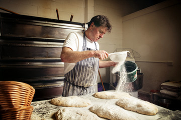 Male baker sprinkling flour on bread dough at bakery