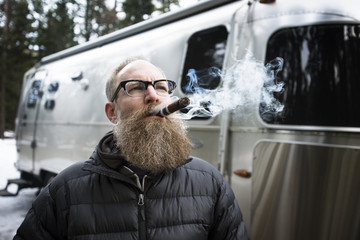 Thoughtful man smoking cigar outside campervan in forest