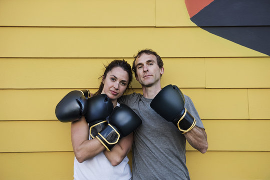 Portrait of confident boxers standing against wooden wall