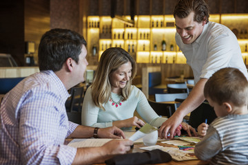 Happy waiter assisting family in reading menu at restaurant table