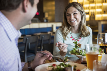 Happy couple talking while having salad in restaurant