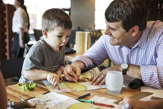 Father and son coloring menu together in the restaurant