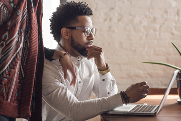 Midsection of woman standing by man using laptop at home