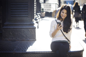 Happy young woman using smart phone on steps outdoors