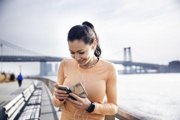 Happy female athlete listening music through smart phone with Williamsburg Bridge in background