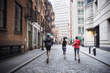 Rear view of multiethnic athletes running on city street