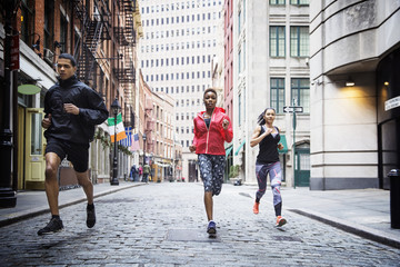 Determined athletes running on city street