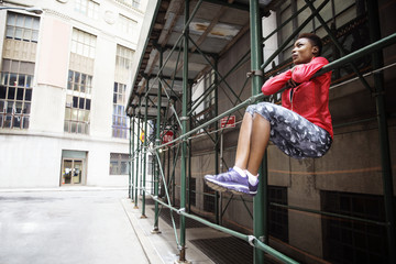 Full length of female athlete hanging on metal rod by city street