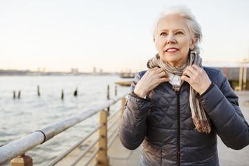 Thoughtful senior woman wearing muffler on promenade during sunset