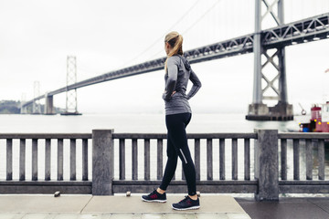 Side view of female athlete looking at Oakland Bay Bridge while standing on footpath