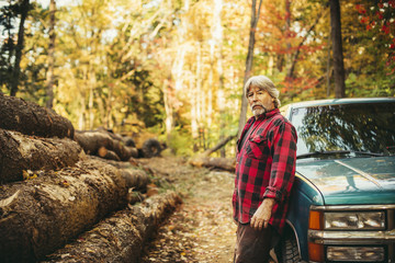 Side view portrait of lumberjack standing by car in forest