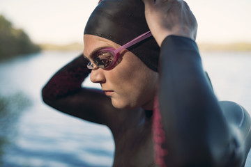 Close-up of female swimmer wearing swimming goggles at lakeshore