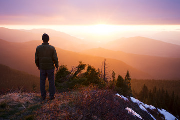 Rear view of hiker standing on mountain during sunset