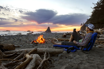 Man sitting by campfire at seashore