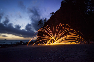 Man spinning wire wool on field at night