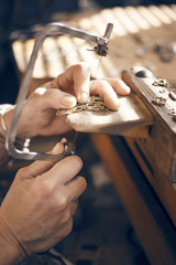 Cropped image of female goldsmith using saw while making jewelry in workshop