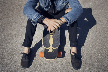 Overhead view of man sitting on skateboard on road
