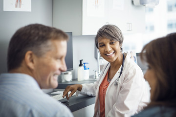 Happy female doctor looking at couple in clinic