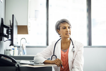 Confident female doctor sitting at desk in clinic