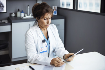 Female doctor using tablet computer in clinic
