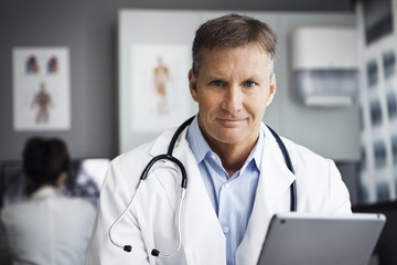 Portrait of confident male doctor holding tablet computer in clinic