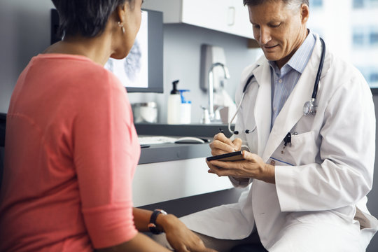 Male doctor writing prescription for female patient in clinic