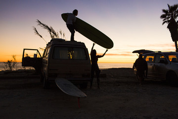 Silhouette of people with surfboard standing on minivan at San Onofre State Beach