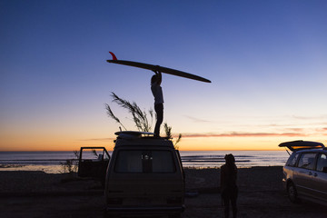 Side view of man carrying surfboard while standing on mini van during vacation with woman on San Onofre State Beach
