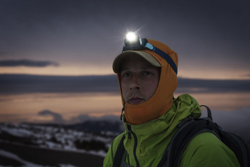 Close-up of man with illuminated headlamp against sky at dusk