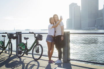 Happy couple taking selfie through mobile phone while standing by Citi Bikes during sunny day