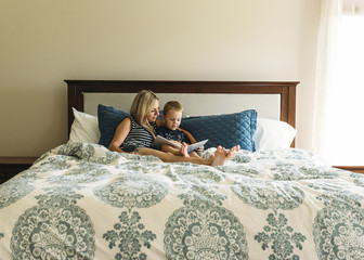 Mother and son reading book while relaxing on bed