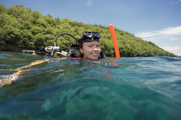Portrait of happy female diver with snorkeling equipment in sea