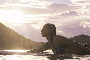 Side view of woman lying on surfboard in sea during sunset