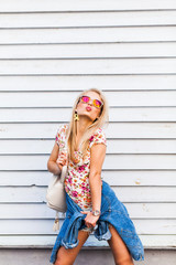 Portrait of a young blonde hipster. Girl with sunglasses dressed in shorts, T-shirt and posing in white wall