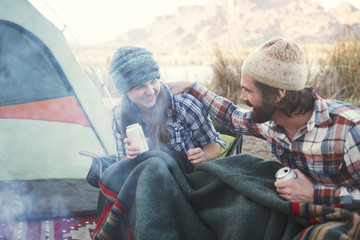 Happy couple holding beer cans enjoying at camp site