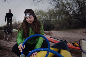 Woman inflating kayak with friends holding dog leash in background at forest