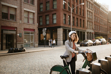 Businesswoman with Citi Bike at parking lot on street
