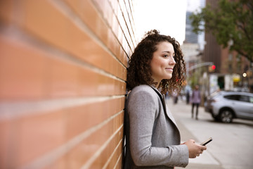 Side view of thoughtful businesswoman holding smart phone while standing by brick wall