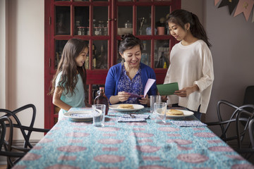 Mother reading greeting cards given by daughters during birthday celebration