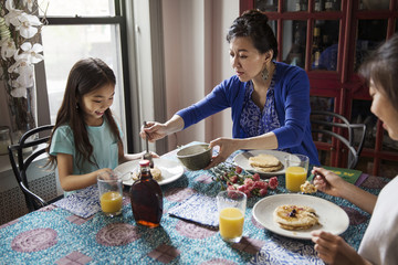 High angle view of mother serving daughter during breakfast
